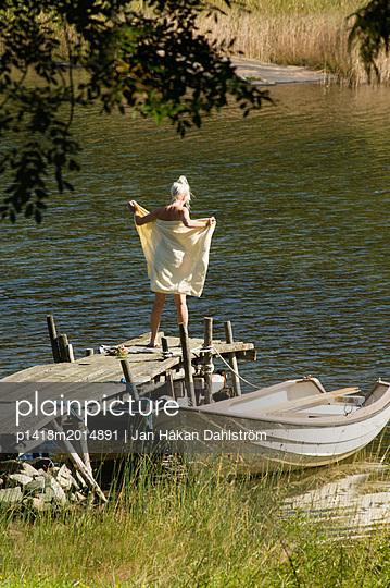 Frau trocknet sich nach dem Schwimmen ab - p1418m2014891 von Jan Håkan Dahlström
