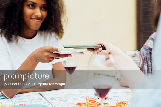 Friends sharing mobile phone while sitting by table - p300m2290651 by Eugenio Marongiu
