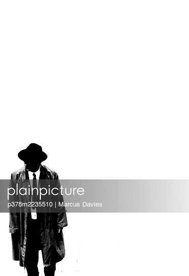Man in long coat and hat - p378m2235510 by Marcus Davies