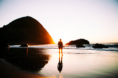 Rear view of man standing at beach during sunset - p1166m1534453 by Cavan Images