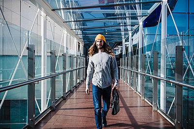 young man with yellow hat on glass bridge at sunset, Madrid, Spain - p300m2274645 von Eva Blanco