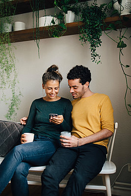 Smiling boyfriend and girlfriend looking at mobile phone while having coffee in living room - p426m2138416 by Maskot