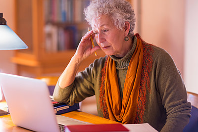 Older mixed race woman using laptop in library - p555m1306136 by Marc Romanelli