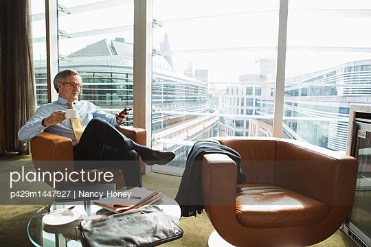 Businessman in coffee area in office, London, UK - p429m1447927 by Nancy Honey