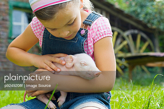 A girl holding a piglet - p9249208f by Image Source