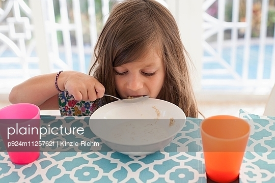 Girl eating breakfast from bowl with spoon - p924m1125762f by Kinzie Riehm