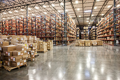 View down aisles of racks holding cardboard boxes of product on pallets  in a large distribution warehouse - p1100m1575462 by Mint Images