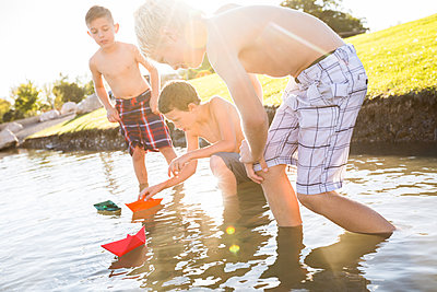 Shirtless friends playing with paper boats in lake - p1166m2011460 by Cavan Images