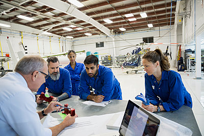 Manager explaining part to mechanics in airplane hangar - p1192m1103557f by Hero Images