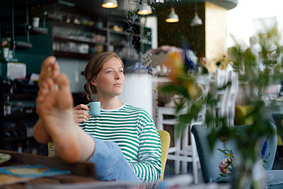 Young woman with feet up holding espresso cup in a cafe - p300m2059290 by Kniel Synnatzschke