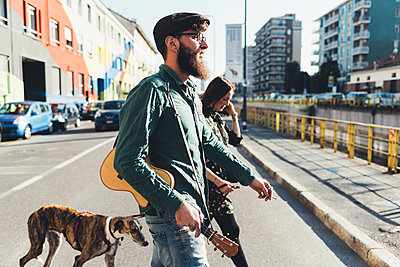 Cool couple walking dog by city canal - p429m1494243 by Eugenio Marongiu