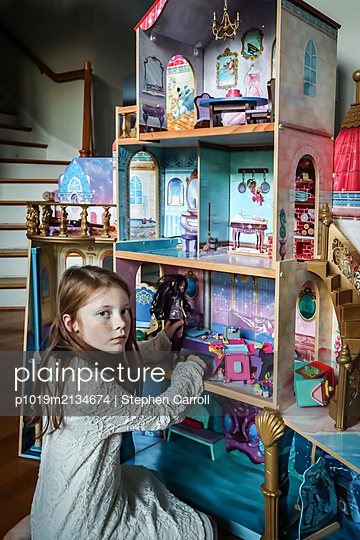 Young girl playing with dollhouse - p1019m2134674 by Stephen Carroll