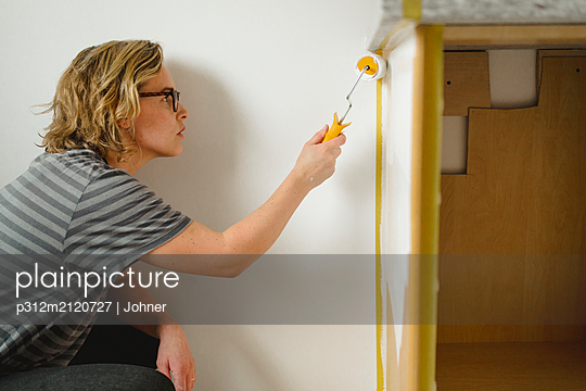 Woman painting cupboard - p312m2120727 by Johner