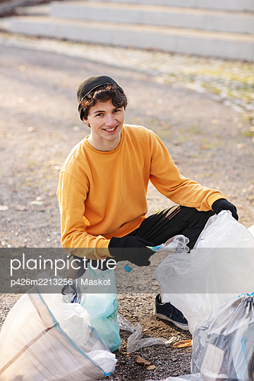 Portrait of smiling male volunteer with plastic waste kneeling on ground - p426m2213256 by Maskot