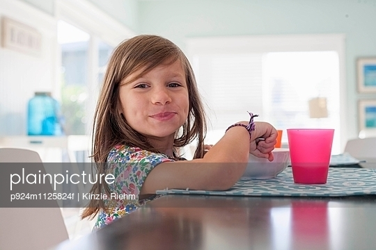 Girl at dining table eating breakfast looking at camera smiling - p924m1125824f by Kinzie Riehm