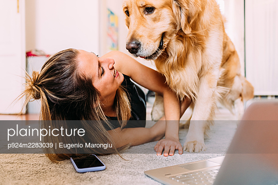 Italy, Young woman with dog at home - p924m2283039 by Eugenio Marongiu