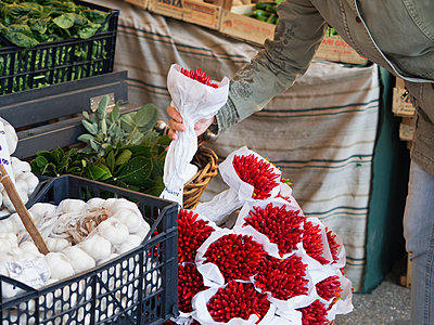 Venice.  A vegetable stall at a street market. A person selecting a bunch of red chillies.  - p1100m1451026 by Mint Images