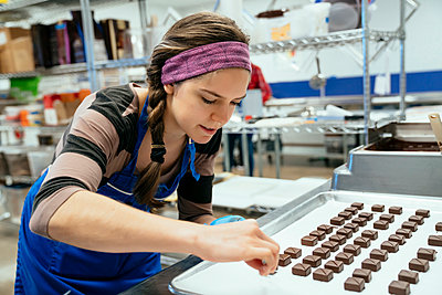 Female chef arranging chocolate pieces in tray at factory - p1166m1555121 by Cavan Images