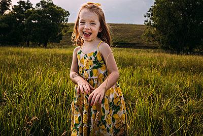 Portrait of happy cute girl standing on grassy field against sky - p1166m2067622 by Cavan Images