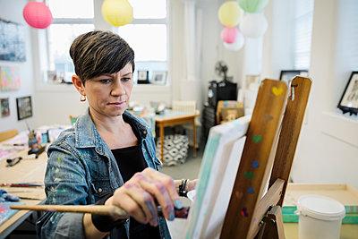 Focused female artist painting in studio - p1192m2066777 by Hero Images