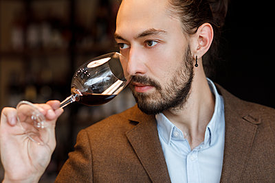 Young man smelling wine in glass at tasting - p1427m2110159 by Mykhailo Lukashuk