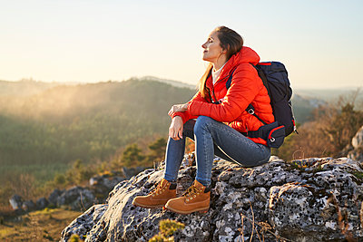 Woman on a hiking trip in the mountains resting on a rock - p300m2083136 by Bartek Szewczyk