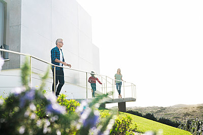 Casual man with his family standing in front of modern home looking at the landscape - p300m2144342 by Steve Brookland