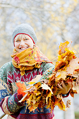 Young cheerful woman holding bunch of autumn leaves - p312m1551991 by Johner Images
