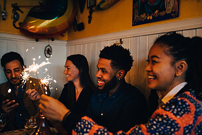 Happy multi-ethnic male and female friends holding burning sparklers in restaurant during dinner party - p426m2046297 by Maskot