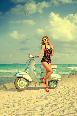 Caucasian woman posing on scooter at beach - p555m1304581 by Chris Clor