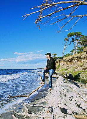 Mann auf Baumstamm schaut aufs Meer - p606m1486778 von Iris Friedrich