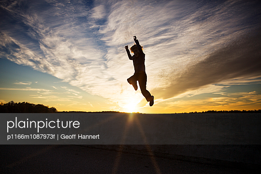 Silhouette of boy (8-9) jumping against sky at sunset - p1166m1087973f by Geoff Hannert