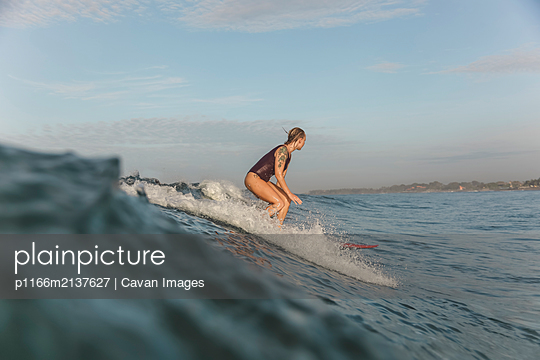 Young woman surfing at sunrise - p1166m2137627 by Cavan Images