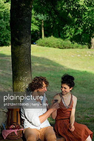 Paar beim Wein auf der runden Gartenbank - p1212m1159045 von harry + lidy