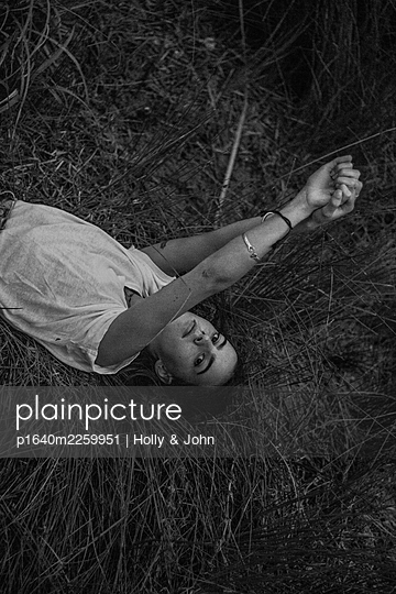 Young woman lying in grass - p1640m2259951 by Holly & John