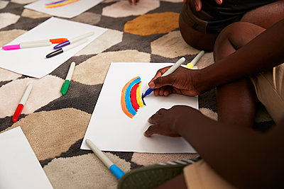 Boy drawing multicolor rainbow with markers on rug - p1023m2238485 by Himalayan Pics