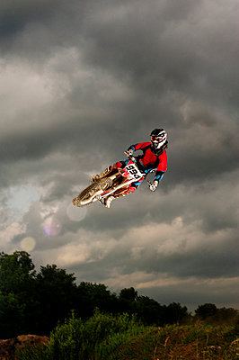 Low angle view of biker performing stunt in mid-air against cloudy sky - p1166m969511f by Cavan Images