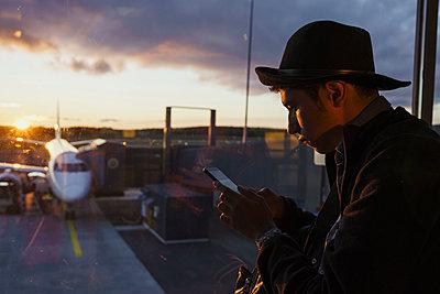 Young man using cell phone at the airport at sunset - p300m2042247 by Kike Arnaiz