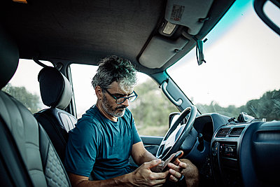 Mature man sitting sitting in his off-road vehicle checking his smartphone - p300m2132271 by Oscar Carrascosa Martinez