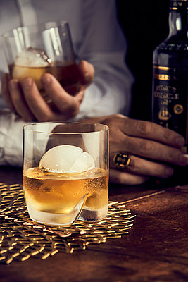 Scotch with ice, mans hands in background - p300m2198012 by PURECREATIONS