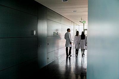 Doctors walking through corridor in hospital - p300m2281513 by Buero Monaco