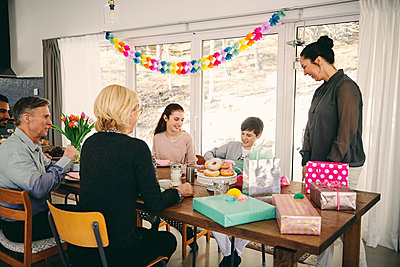 Family looking at boy with gift box while enjoying meal at table during birthday party - p426m1580229 by Maskot