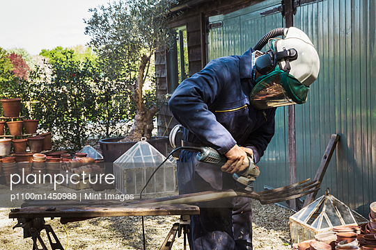 Man standing outdoors, wearing a face mask, working on a metal pitchfork with an angle grinder. - p1100m1450988 by Mint Images