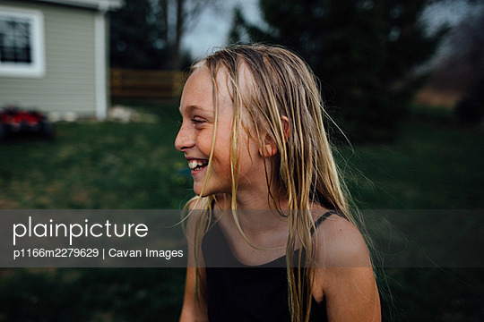 young girl laughing with wet hair - p1166m2279629 by Cavan Images