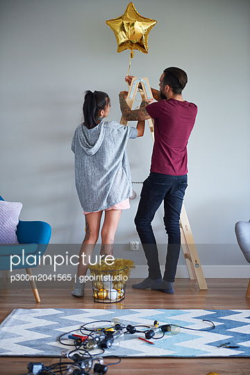 Modern couple decorating the home at Christmas time using ladder as Christmas tree - p300m2041565 von gpointstudio