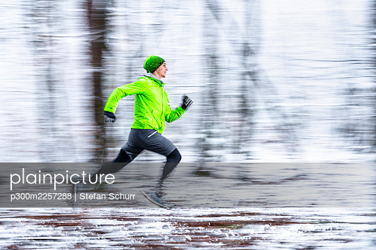 Young sportsman running in speed at forest during cold temperature - p300m2257288 by Stefan Schurr