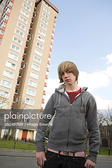 Boy by tower block - p9248766f by Image Source