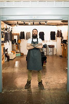 Portrait confident leather shop owner entrepreneur - p1192m1145611 by Hero Images