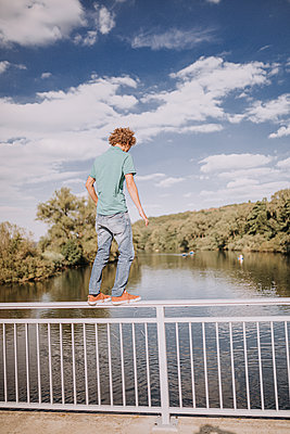 Young man standing on the railing of a bridge - p1267m2259709 by Jörg Meier