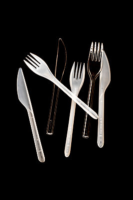 Six disposable plastic white and transparent knives and forks on a black background - p1302m2044573 by Richard Nixon